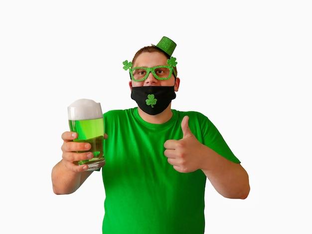 Um jovem com um chapéu de duende comemora o dia de são patrício um irlandês bebe cerveja verde