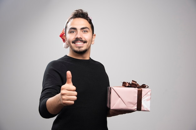 Um jovem com um chapéu de papai noel aparecendo um polegar e segurando um presente.