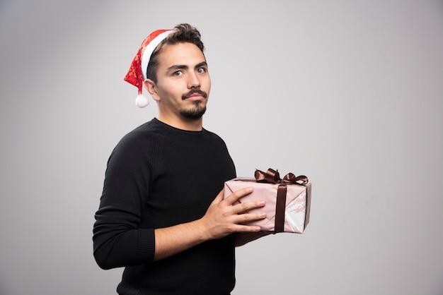 Um jovem com um chapéu de papai noel segurando um presente de ano novo.