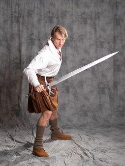 Um jovem com um kilt de couro e uma blusa de renda branca em postura de combate