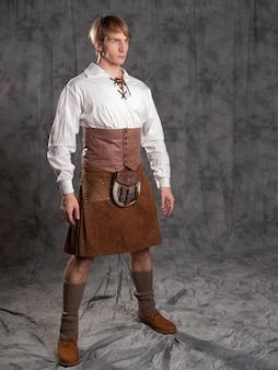 Um jovem com um saiote de couro e uma blusa branca com cordões. um cavaleiro escocês