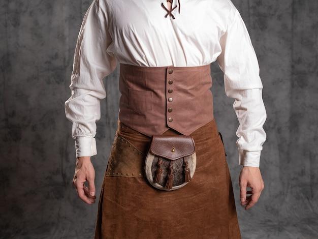 Um jovem com um saiote de couro e uma blusa branca com cordões. um kilt escocês marrom com um cinto e sporran, uma bolsa de cinto. fechar-se