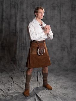 Um jovem com um saiote de couro e uma blusa branca rendada - um cavaleiro escocês