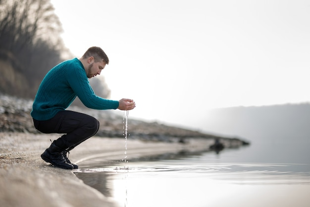 Um jovem com um suéter turquesa molha as mãos no rio