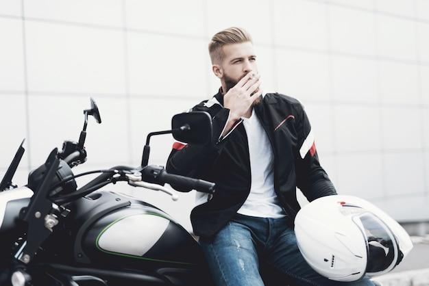 Um jovem com uma barba senta-se em sua motocicleta elétrica.