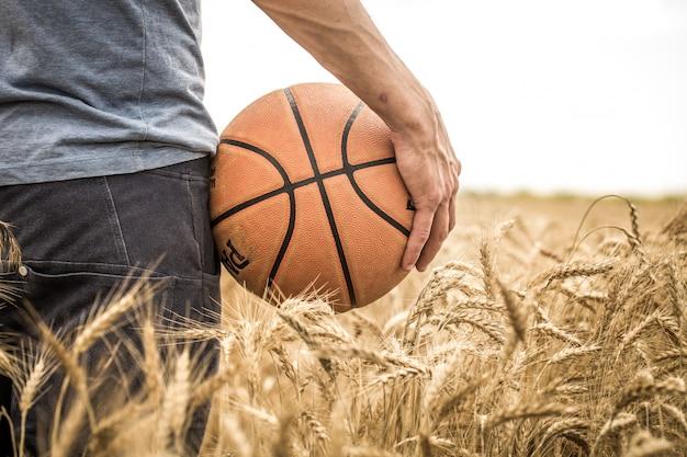 Um jovem com uma bola de basquete na natureza, conceito de esporte