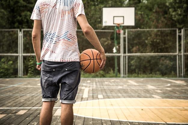 Um jovem com uma bola de basquete na quadra, o conceito de esporte
