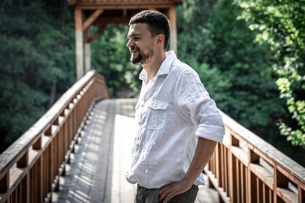 Um jovem com uma camisa fica em um motu de madeira na floresta.