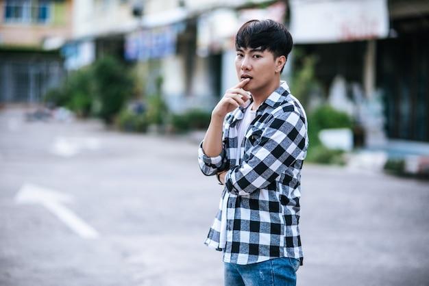 Um jovem com uma camisa listrada está parado na rua.