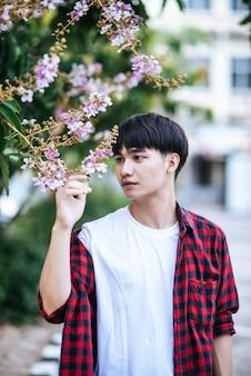 Um jovem com uma camisa listrada estava parado na beira da estrada segurando a flor.