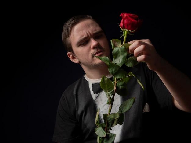 Um jovem com uma camiseta preta segura uma rosa vermelha nas mãos e examina