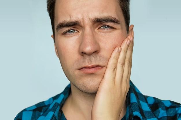 Um jovem com uma emoção triste no rosto, segurando a mão sobre a mandíbula do paciente em um fundo azul. retrato de um homem com expressão dolorosa e dor de dente.