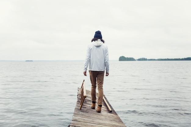 Um jovem com uma jaqueta caminha ao longo de uma ponte de madeira no lago. bela paisagem calma. vista traseira. turismo e viagens.
