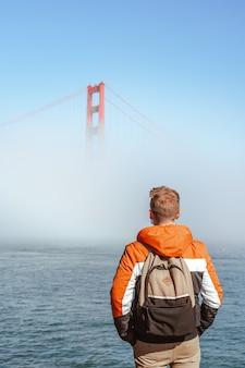 Um jovem com uma jaqueta está parado no aterro e olha para a névoa cobrindo o portão dourado