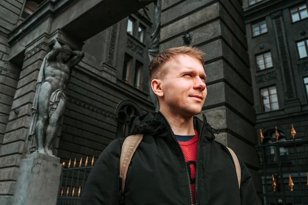 Um jovem com uma jaqueta na parede de um edifício histórico escuro com esculturas em são petersburgo