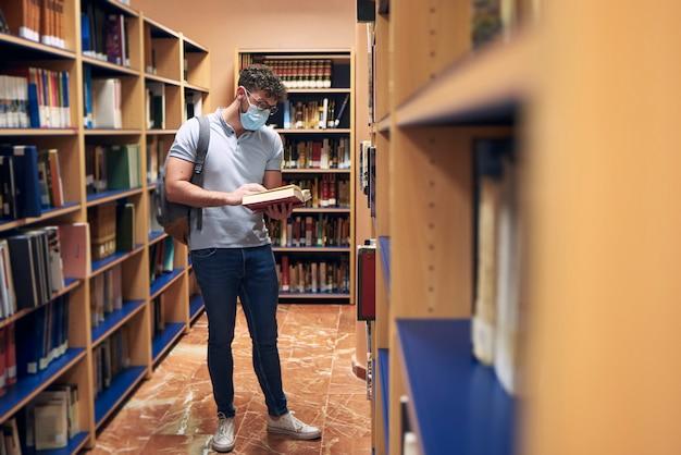 Um jovem com uma máscara está lendo um livro na biblioteca
