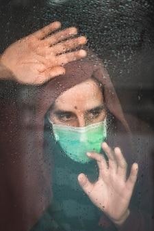 Um jovem com uma máscara na pandemia de covid-19, olhando através de uma janela