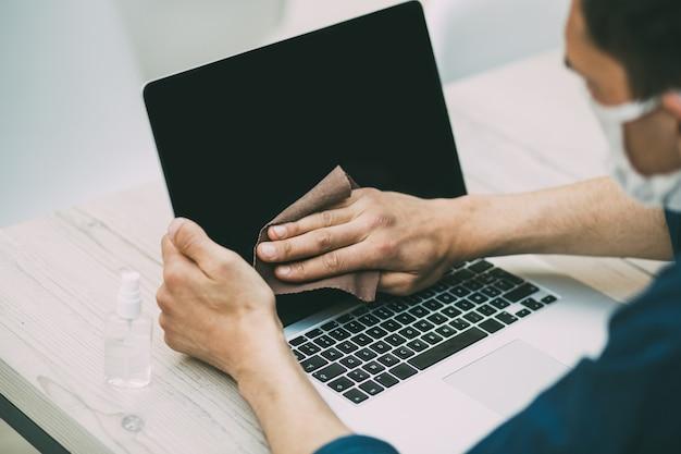 Um jovem com uma máscara protetora limpando a tela de seu laptop