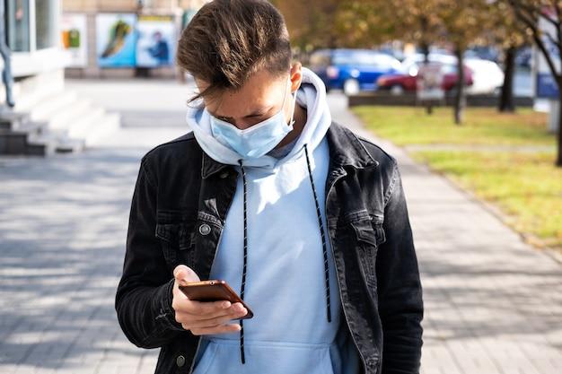 Um jovem com uma máscara protetora na rua fica de pé e olha para um smartphone.