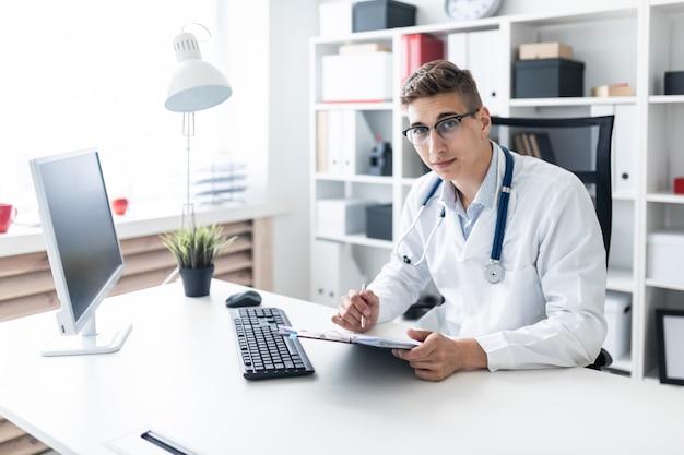 Um jovem com uma túnica branca, sentado a uma mesa no escritório. ele está segurando uma caneta e um tablet com documentos.