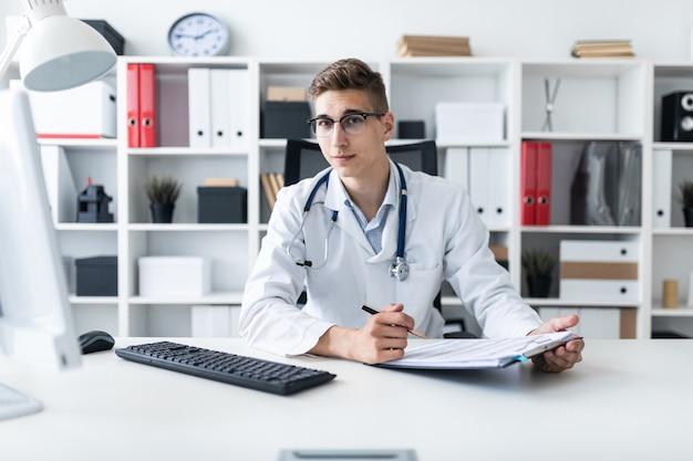 Um jovem com uma túnica branca, sentado a uma mesa no escritório. ele segura uma caneta na mão e parece reto. o retrato do médico.