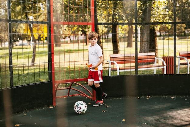 Um jovem com uniforme esportivo treina com uma bola na quadra de futebol estilo livre.