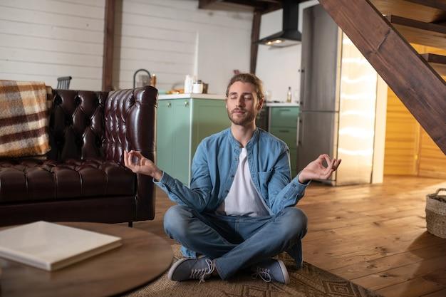 Um jovem concentrado praticando meditação em casa