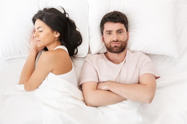 Um jovem confuso e descontente deitado na cama, debaixo do cobertor, perto de uma mulher adormecida
