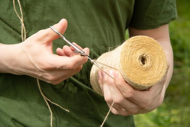Um jovem corta um fio do toco com uma tesoura de um babuíno redondo