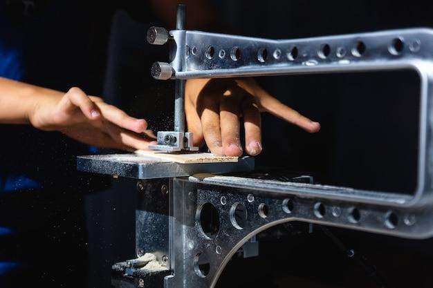 Um jovem corta um padrão na madeira compensada com uma serra elétrica