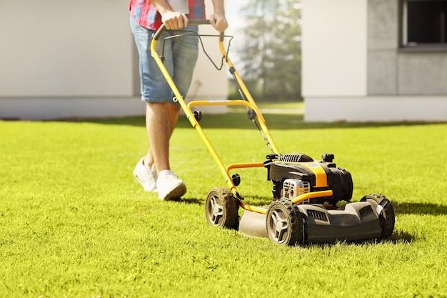 Um jovem cortando a grama
