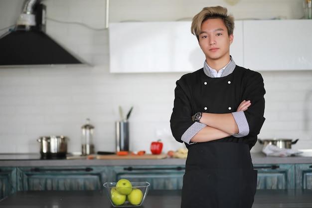 Um jovem cozinheiro asiático na cozinha prepara comida em um traje de cozinha