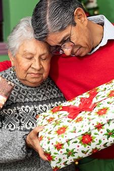Um jovem dando um abraço e um presente para a avó no natal