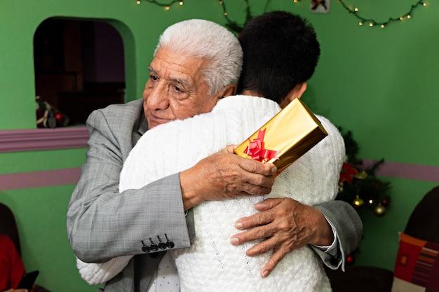 Um jovem dando um abraço e um presente para seu avô no natal