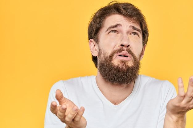 Um jovem de barba em uma camiseta mostra emoções diferentes, diversão, tristeza, raiva