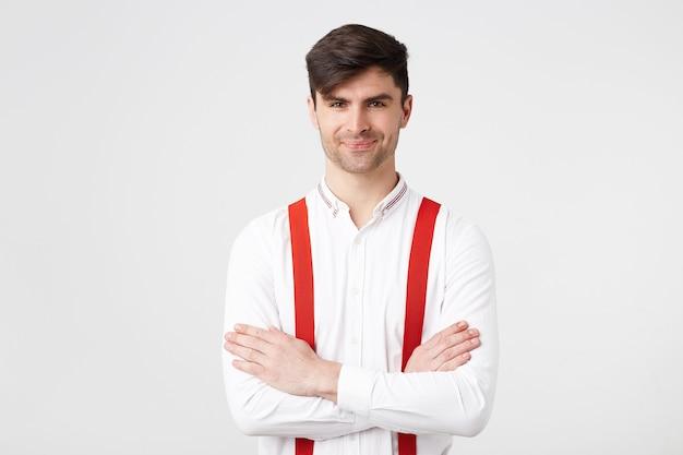 Um jovem de cabelo escuro com a barba por fazer em pé com os braços cruzados, vestindo uma camisa branca