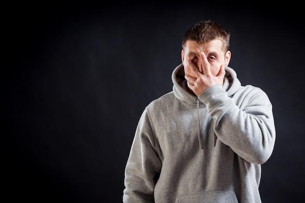 Um jovem de cabelos escuros com uma camiseta esportiva cinza ficou doente com um resfriado