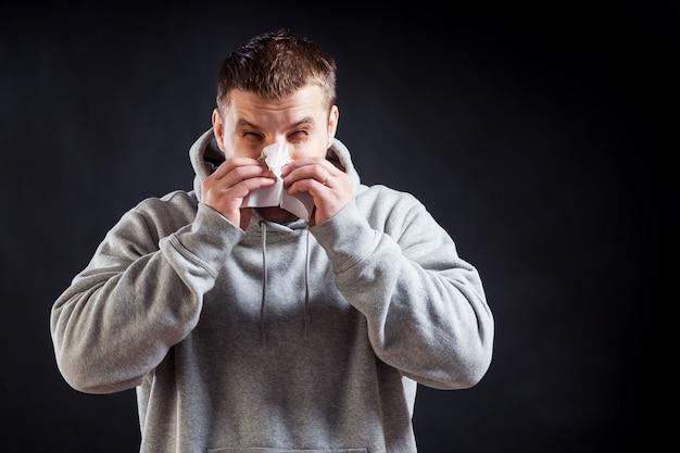 Um jovem de cabelos escuros em um moletom cinza esportivo ficou doente com um resfriado, o nariz está entupido