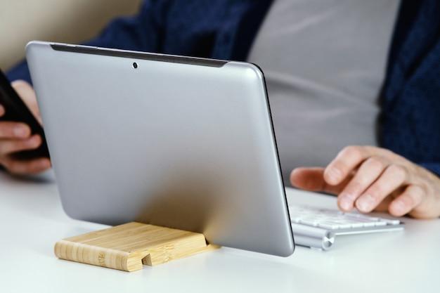 Um jovem de camisa azul está sentado em sua mesa
