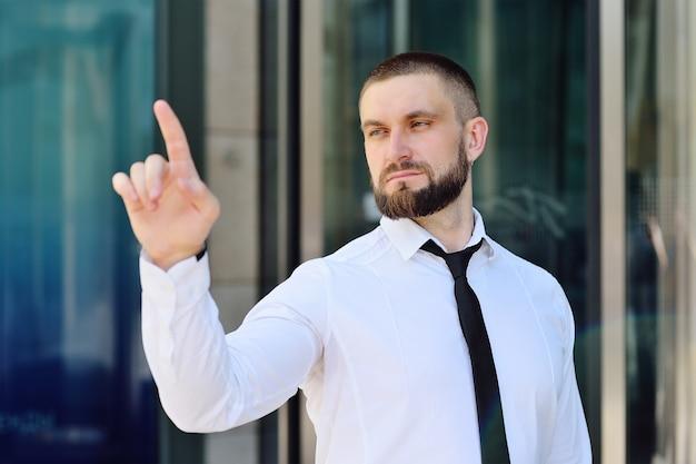 Um jovem de camisa branca e gravata está pressionando o dedo indicador na tela virtual da tela de toque