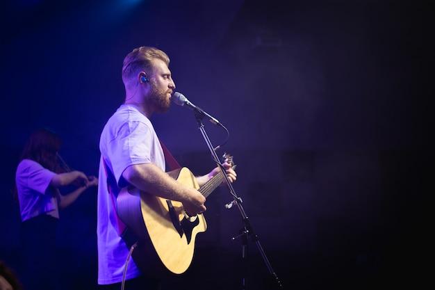 Um jovem de camiseta branca com barba segura um violão na mão e canta em um microfone no palco