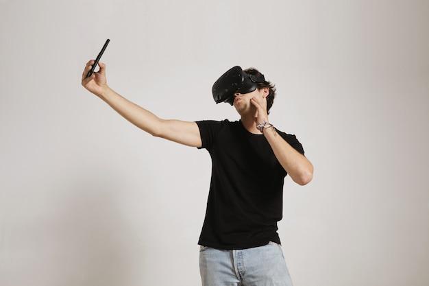 Um jovem de camiseta preta e jeans usando um fone de ouvido vr faz uma cara de pato enquanto tira uma selfie com seu smartphone, isolado no branco