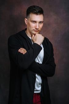 Um jovem de jaqueta preta e camiseta branca fica de pé e olha em frente com um olhar inteligente