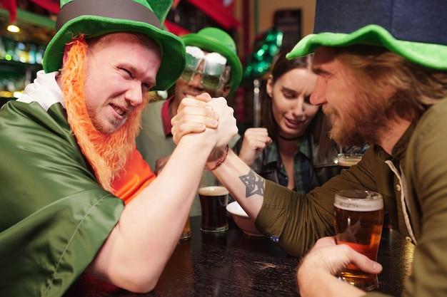 Um jovem de mãos dadas e competindo entre si durante uma queda de braço em uma mesa de bar