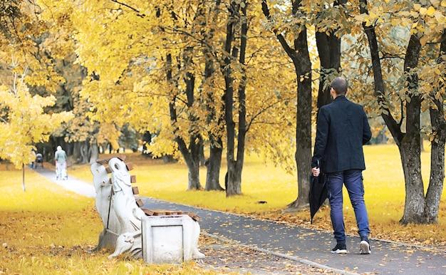 Um jovem de óculos anda no parque com um guarda-chuva durante a chuva.