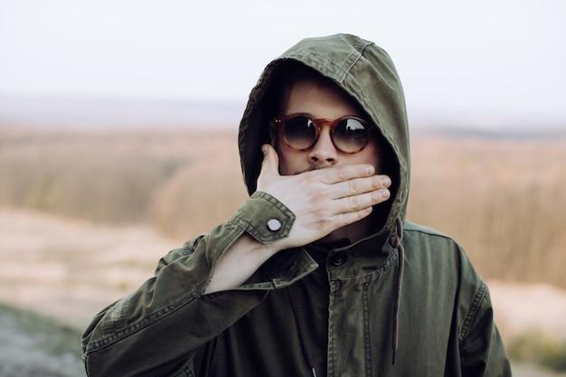 Um jovem de óculos cobriu o rosto com a mão