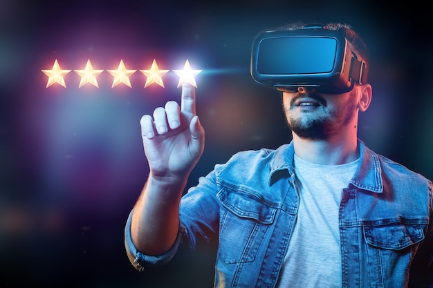 Um jovem de óculos de realidade virtual coloca 5 estrelas, atribuindo uma nova classificação, serviços de classificação, um novo nível, conceito de negócios.