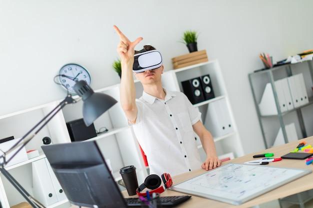 Um jovem de óculos de realidade virtual fica perto da mesa e levanta o braço. um jovem manuseia uma página virtual.