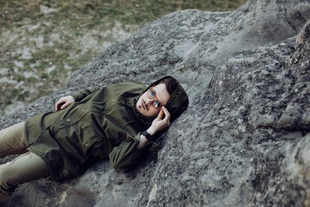 Um jovem de óculos de sol encontra-se em uma pedra nas montanhas. conceito de viagens