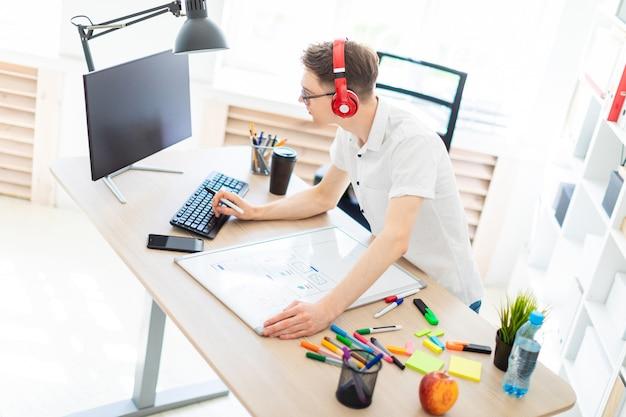 Um jovem de óculos e fones de ouvido fica perto de uma mesa de computador, segura um marcador na mão e imprime no teclado. diante dele está um quadro magnético e marcadores.